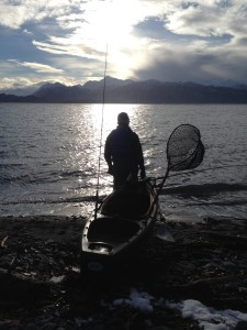 Sillhouette of Ben on the beach by Land's End getting ready to launch the kayak.
